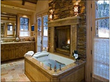 Master Suite Bathroom With A Built In Fireplace Over Tub.