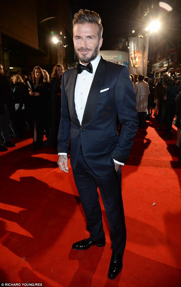 The most debonair of gents: David Beckham arrived to a backdrop of screams in a striking navy blue and black suit at theEE British Film Academy Film Awards in London on Sunday evening
