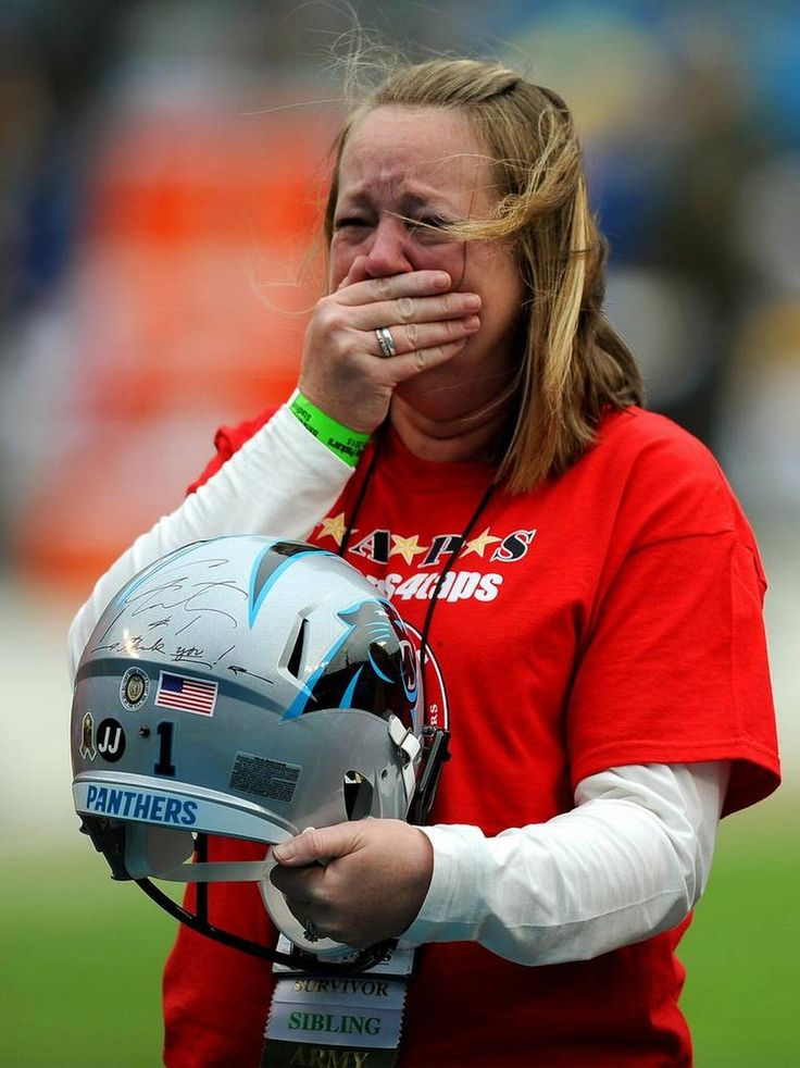 Lisa Winn of Varnville, SC cries as she holds a Panthers replica helmet signed by Carolina Panthers quarterback Cam Newton that was presented to her in honor of John Jarrell on Sunday, November 8, 2015. To honor the memory of those who died in service to our country, Carolina Panthers players wore a decal with the initials of a fallen service member on their helmets when they faced the Green Bay Packers
