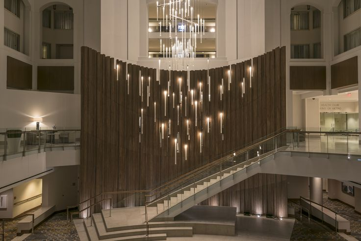 The distinguished Grand Hyatt hotel in Washington DC sought to bring back the luster and excitement to its landmark property. Knowing this, we proudly stepped in to provide the new multistory focal lobby chandelier - the tallest one of its kind standing 50 meters tall in combined height. Each hanging section carries 272 glass tubes covered Stardust® on the inner surface to better distribute the light. #design #light #lighting #chandelier #elegance #hotel #hospitality #lobby