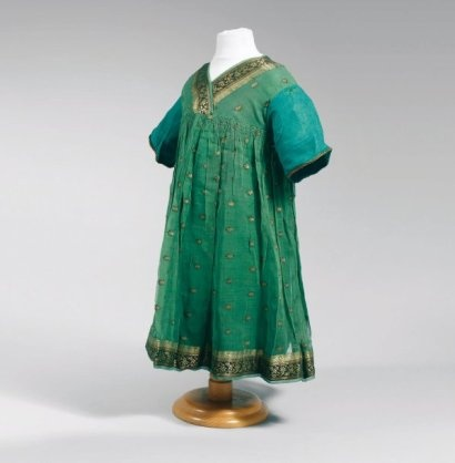 Paul Poiret, circa 1920  DRESS GIRLS green cotton gauze pads over embroidered with gold borders scrolls also woven gold on green background, small necklines cross points to the effect of high gathered waist giving the fullness of the skirt, capped sleeves gauze united another ending with a green metallic old gold braid.