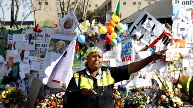 A well wisher wearing ANC colors gestures in front of the Medi-Clinic Heart Hospital, where the ailing former South African President Nelson Mandela is being treated at, in Pretoria, July 9, 2013.