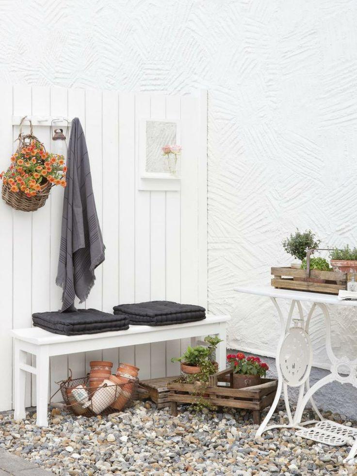 HÅNDKLESTASJON: Har du utebad eller utedusj, er det fint å lage til en stasjon for vask og tørk, med de nødvendige ingrediensene: håndlær, såper og svamper. Pynt med noen blomster. Rullesteiner som underlag i hagen er både praktisk, pent og godt å gå på, altså et material man kan vurdere for flere bruksområder i hagen.