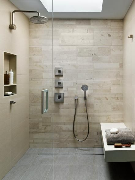 """Not only overflowing with pampering amenities — multiple shower heads, a built-in bench, integrated storage niches — this walk-in spa shower boasts green cred, to boot: """"The luxe-looking limestone wall tile is actually Lithoverde, the only natural stone comprised of 99-percent post-industrial recycled and reclaimed material,"""" says architect Kevin Yoder. A skylight floods the shower with sunshine, a feature the owners cite as one of their favorites."""