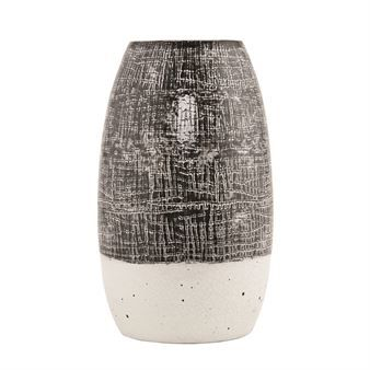 Diced vase from House Doctor has a rustic look that brings thoughts to ceramic from the 60s and 70s. It´s made in clay and has an elegant rounded shape. The bottom is glazed in a light color while the top has a stylish pattern in a grey brown tint. A nice interior detail that suits perfect in a shelf, on a table or a side board!