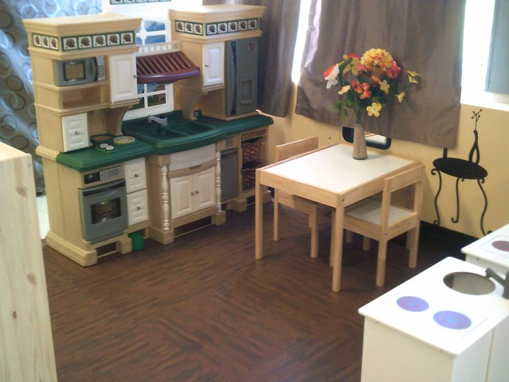 Educare (Johnstown)- A kitchen area in this toddler program reflects the aesthetics of home, including flowers on the table and neutral coloured furniture, walls and curtains.