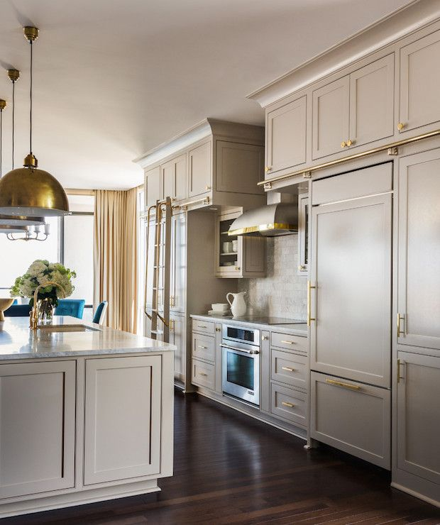 Beautiful kitchen features greige cabinets painted Sherwin Williams Anew Gray paired with marble countertops and a linear marble Kohler Essex Faucet in Brushed Gold.