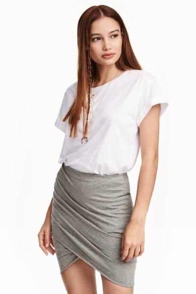 Юбка с драпировкой: Короткая трикотажная юбка с драпировкой и запахом спереди. На юбке потайная резинка на талии.