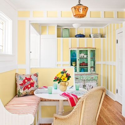 Original board-and-batten walls in a sunny yellow enclose a new eating nook that fits seamlessly into this circa 1913 bungalow.
