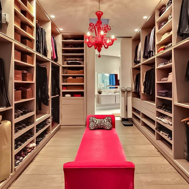 neutral closet with pops of red leading into a bathroom at the far end.