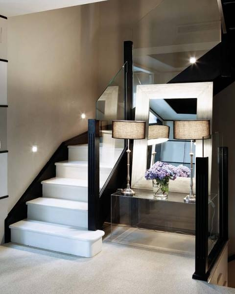 stairs, lucite/glass console table with leaning mirror and lamps