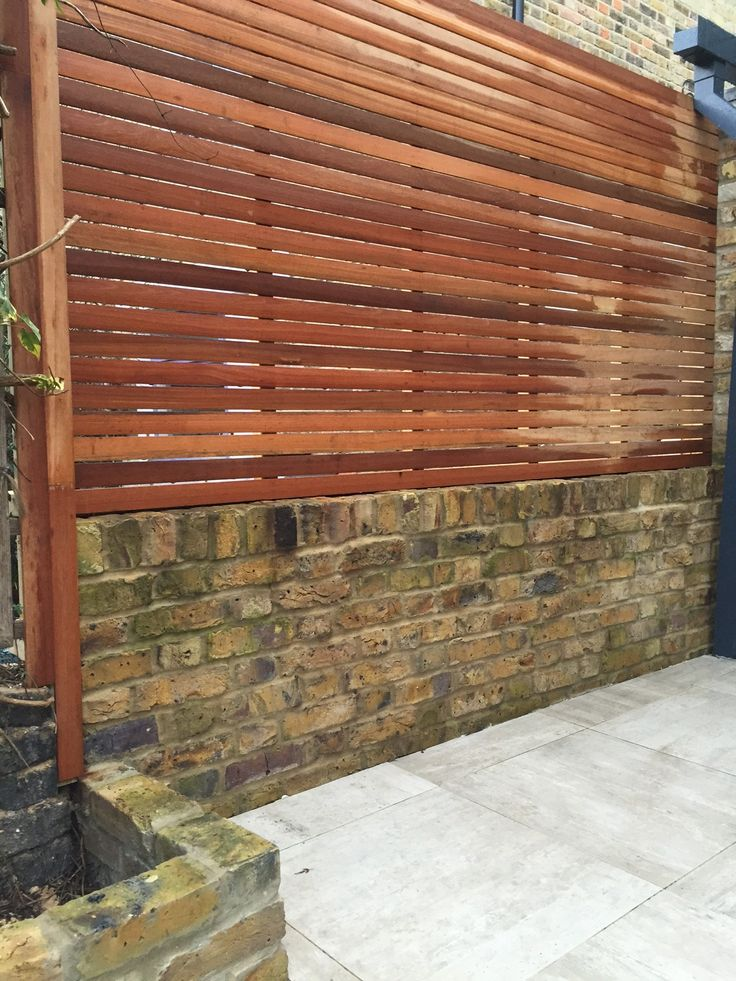 hardwood screen trellis on yellow stock brick wall london
