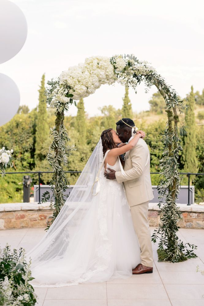 First kiss shot in front of ceremony altar made from hydrangea and eucalyptus