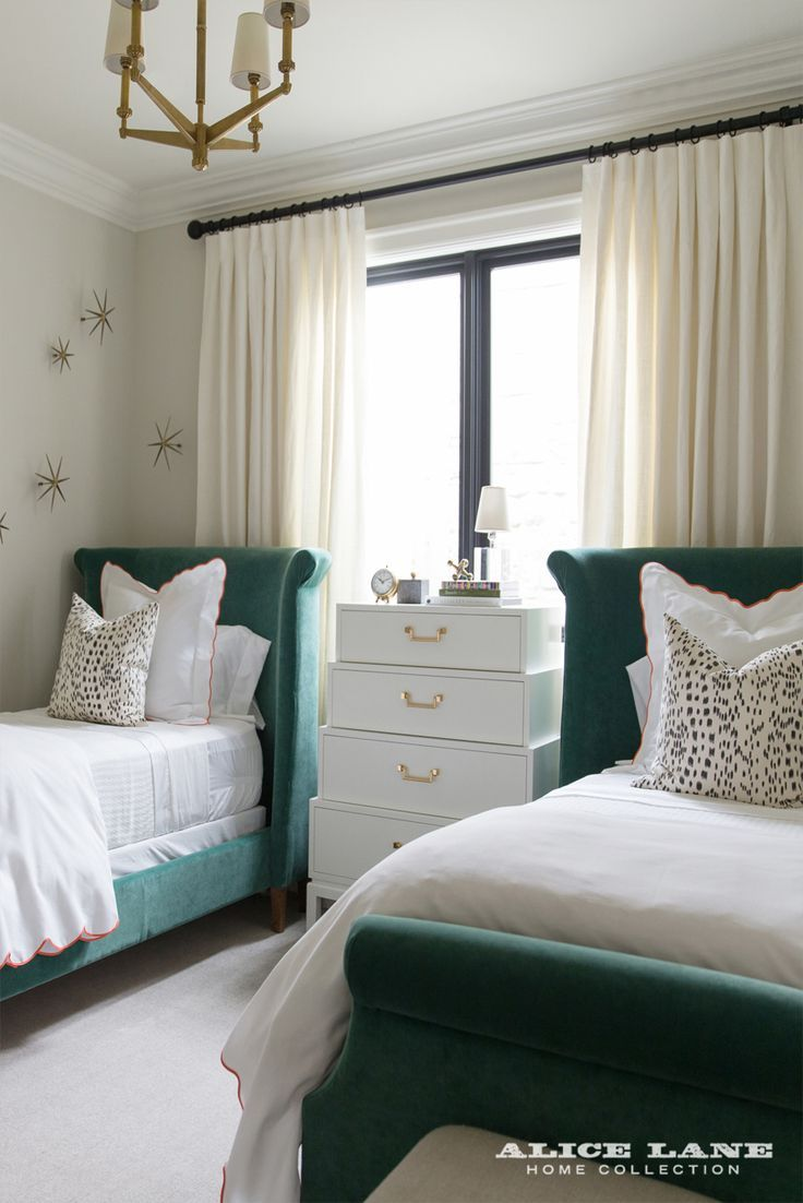 A whimsical and chic guest bedroom! A lovely pair of customized, green velvet beds nestled between a white chest of drawers. The room is complete with decorative starburst wall art and hints of salmon. | French Modern Manor Designed by Alice Lane