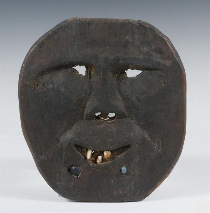"19th c. Carved Wood Plank Mask with features defined in shallow relief, eye and nose openings, smiling mouth with inset teeth, two inset trade beads, 9 1/4"" x 8"", 3/8"" thick"