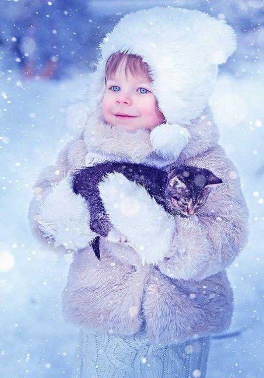Niña en la nieve con un gato en sus brazos