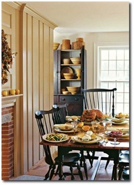 FARMHOUSE – INTERIOR – vintage early american farmhouse showcases raised panel walls, barn wood floor, exposed beamed ceiling, and a simple style for moulding and trim, like in this farmhouse with primitive and colonial decorating.