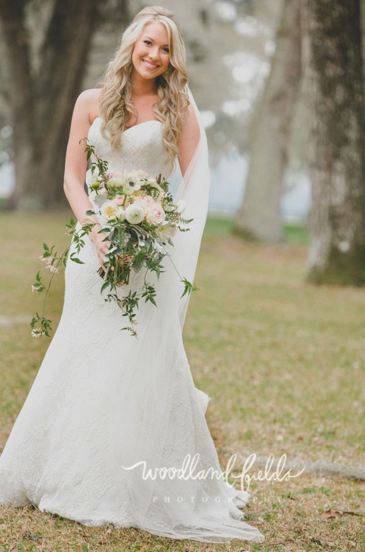 the bride carries her bouquet of kiera garden roses, light pink ranunculus, white ranunculus, white veronica, white anemone, patience garden roses, cafe au lait dahlia, jasmine trails, dusty miller, fern & greenery wrapped in green gingham check ribbon