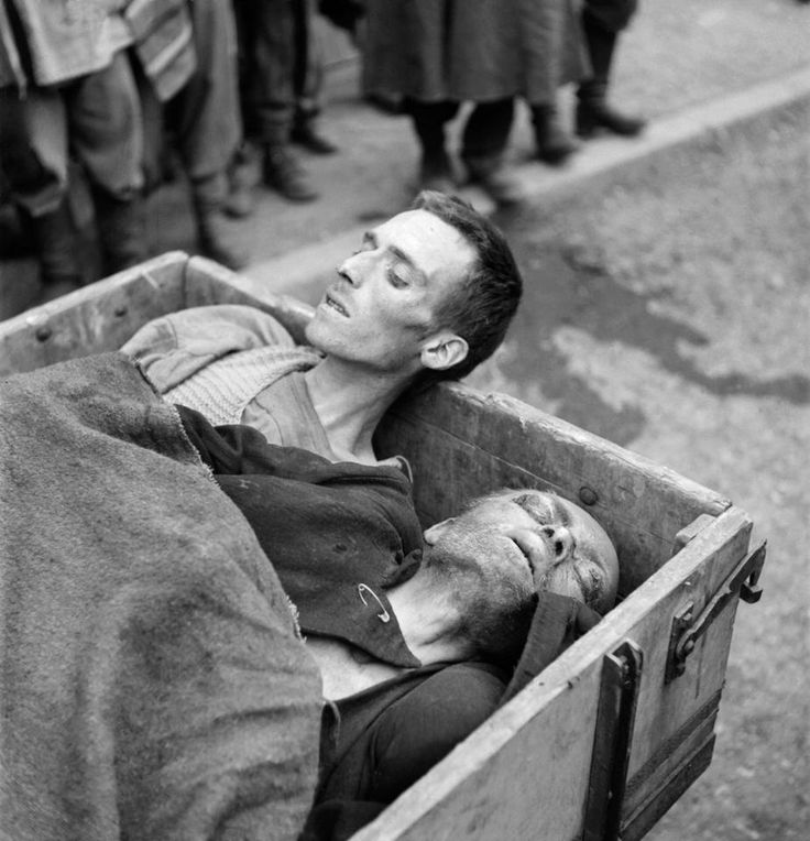 Two dead prisoners are taken away in a cart after Dachau was liberated by U.S. troops, photographed by Eric Schwab (May 1945). U.S. soldiers arrived to find surviving prisoners, as well as a number of unburied bodies left by fleeing SS guards.