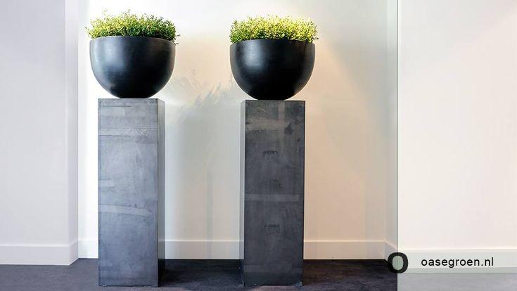 Zwarte ronde pot met daarin groene kunstbeplanting op een grijze zuil. Met @Maxifleur Kunstplanten