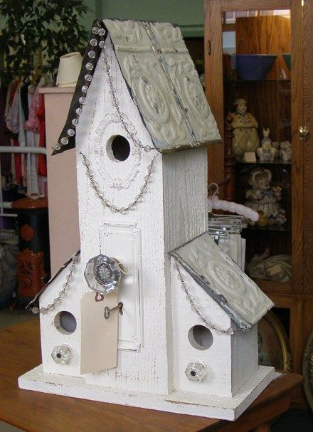 This 'upcycled' birdhouse is decorated with vintage odds and ends, bringing a touch of whimsy and originality to any garden.