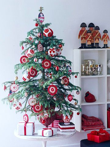 Decorations with a consistent theme -- red and white -- make a graphic statement on this tabletop tree. To show off your ornaments, choose a tree with short needles and sparse branches, and don't be afraid to trim boughs to create display space.