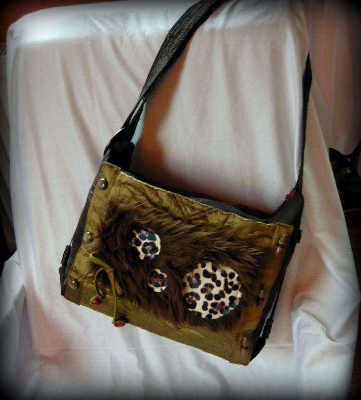 Leopárd-szőrmés táska -Handmade by Judy Majoros: A táska külseje barna nyomott mintás pamutszövet, az elején zöld szaténból készült egy zseb, azon pedig barna műszőrméből egy kisebb. A műszőrmére leopárd mintás textilbőrből készültek pöttyök, valamint egy masni. Hátsó részén egy nagyobb cipzáras zseb található. Belseje bordó kordbársony bútorszövettel bélelt, és 2 nagy + 1 kis zseb található benne. A táska teteje bordó cipzáras záródást kapott. Pántja barna csipkével díszített.