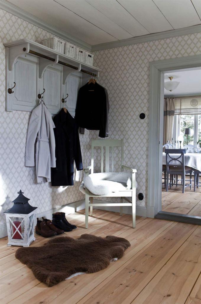 <span>Lantlig stil i hallen. Den snygga hängaren är köpt i butiken Jacob & Mary i Vadstena. Tapeten kommer från Sandbergs.</span>