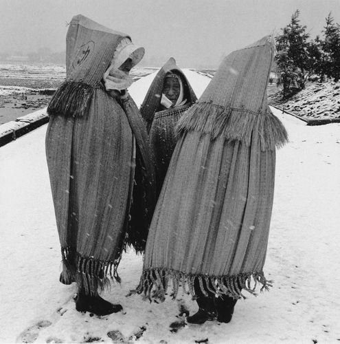 Walking Home in the Snow, Yamagata-ken. Rural women in Japan sometimes still wear straw raincoats. Linda Butler Photography.
