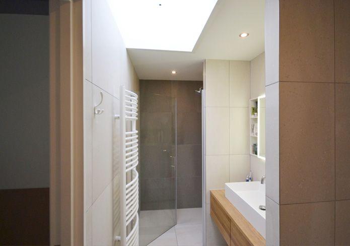 Ondanks de beperkte afmetingen heeft deze badkamer een ruimtelijke, lichte en luxe uitstraling. De grote tegels in twee verschillende kleuren geven de badkamer meer diepte. De kasten (houtmerk) zijn opgenomen in de wanden zodat de badkamer rustig oogt.