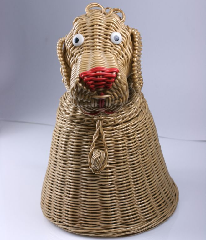 """Charming and goofy """"hound dog"""" purse from the 1950s. Laminated wire to resemble wicker is handwoven in this construction. Hand painted button eyes and contrasting red snout. Braided handle and self button at neck opens head to enter purse. Delightful and demented picnic fare.    12"""" x 8"""" handle 20"""""""