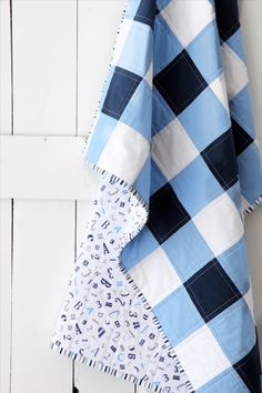 This simple gingham quilt by Elaine of Beech Tree Lane Handmade is darling! For her fabrics she used Robert Kaufman Fabrics Kona Solids in Navy, Candy Blue and White to achieve the signature gingham pattern. The backing is ABC/123 in Blue by Quilting Treasures, and the binding is a coordinating stripe also by Quilting Treasures. She sandwiched Warm and White 100% cotton batting by The Warm Company, and quilted everything together with Aurifil 2024.