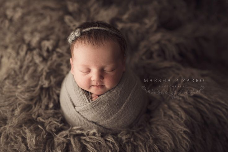 newborn baby girl in potato sack pose wrapped in grey on matching flokati
