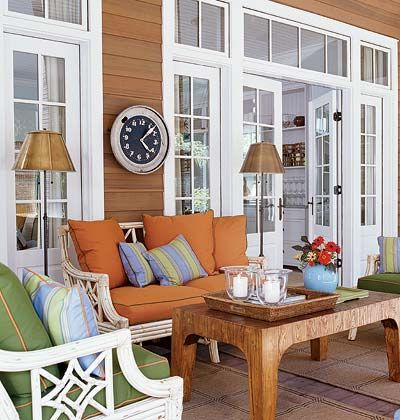 A porch with brightly colored fabric cushions and sea grass rugs.