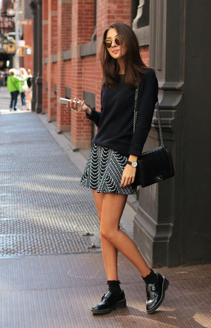 Felicia Akerstrom is wearing a black and white skirt from Zara, black sweater from Uniqlo, bag from Chanel, and the shoes from Ash