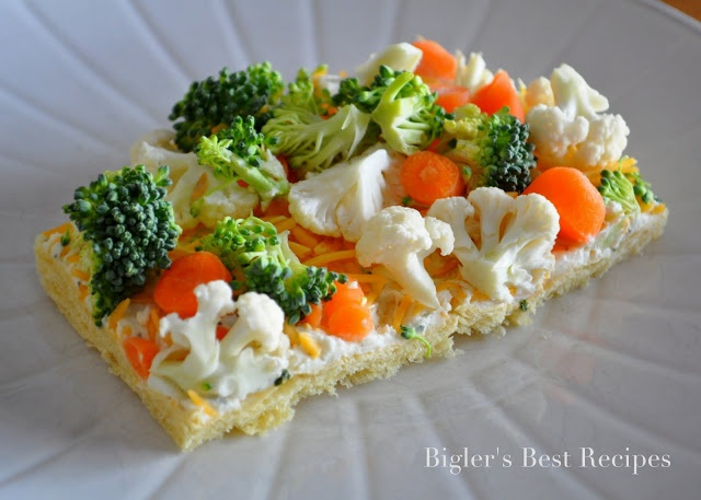 I forgot about these vegee bars! soo good! Spread out 2 (8oz) packages of refrigerated crescent roll dough onto an 18x12 cookie sheet. Bake at 375 for 10-13 min. Let cool.   Mix 6 oz. cream cheese with 1 oz. ranch dressing powder (1 packet). Spread on cooled crescents. Top with shredded cheddar cheese and veggies of your choice. Great with broccoli, cauliflower,carrots, bell pepper, sweet peppers, etc (make sure to cut them into very small pieces).