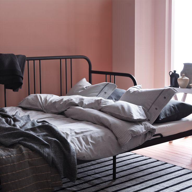 En dagbädd i svart metall, här som en soffa med grå kuddar.