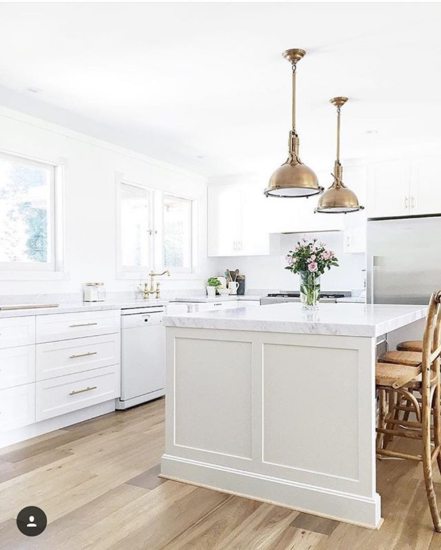 All white kitchen with gold and brass accents. White shaker style cabinets, light hardwood floors, and industrial gold dome pendants.
