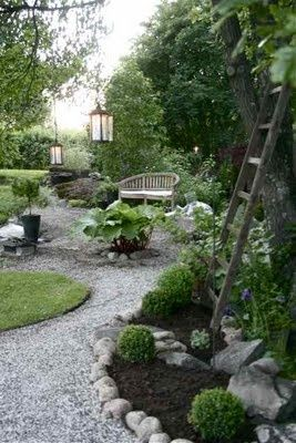 Gravel path  boxwood balls, love the ladder and the lanterns hanging from the trees!