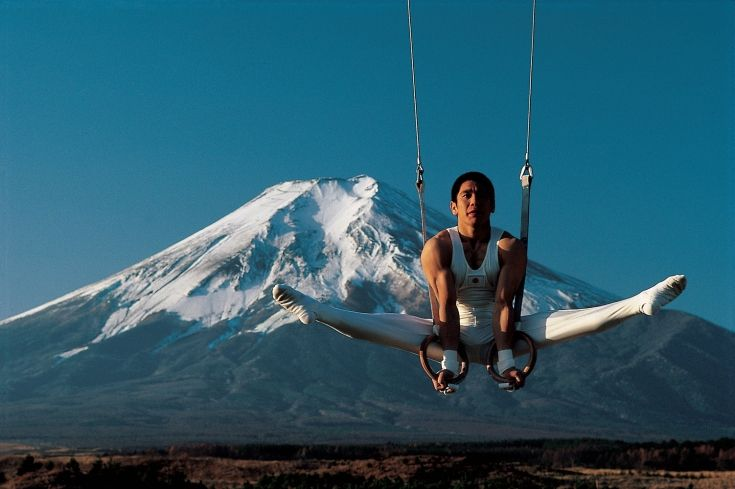 Neil Leifer's 1984 Olympic Odyssey Around the World - athletes in front of famous landmarks - Koji Gushiken on rings in front of Mount Fuji, Japan