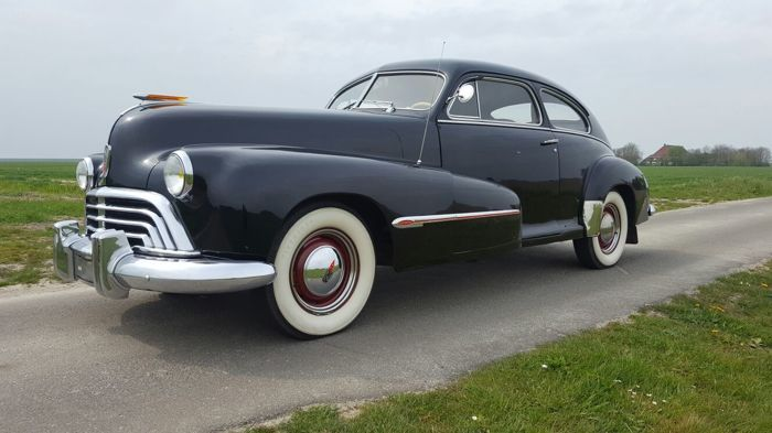 Cette Oldsmobile 2 portes de 1947 a une immatriculation néerlandaise. Une voiture dure qui roule, tient la route, freine et embraye bien. Il y a une transmission automatique Hydromatic, c'était l'une des premières transmissions automatiques à l'époque. Le moteur d'origine est un 6 cylindres en ligne avec une capacité de 238ciu. elle fonctionne très bien. Sur le plan technique et mécanique en très bon état, esthétiquement très belle voiture à voir, il y a une différence de couleur dans la…