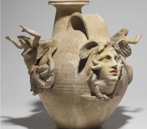 Canosan pottery askos, 4th-3rd century B.C.The large spherical body on a flat base, with a wide strap handle and a cylindrical spout, the rim flaring, a mold-made facing head of Medusa applied to the body below the spout and on the opposite end, a snake extending onto her cheeks, their tails knotted low on her neck, each side of the vessel with a figure of a Tritoness, her arms upraised, preserving extensive polychrome, including yellow, red, pink and blue, 49 cm high. Private collection
