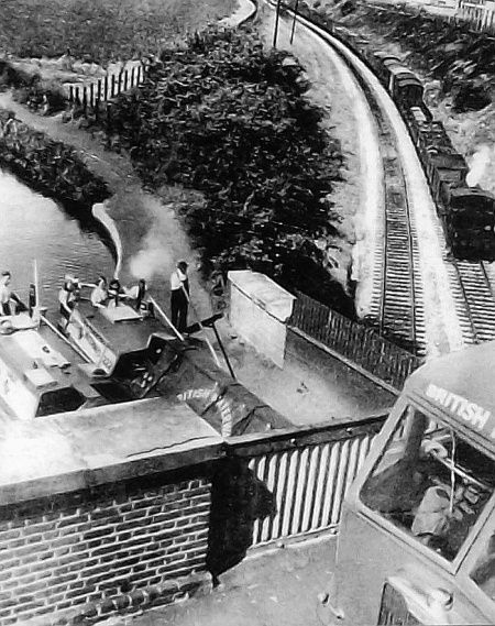 """Caption: """"Three Bridges, Hanwell  ― the Canal crosses the railway  in an 8 ft-wide cast-iron trough aqueduct."""" #london #canal #middlesex #hanwell #railway #road #narrowboat #barge #lorry #train #publicity #photograph"""