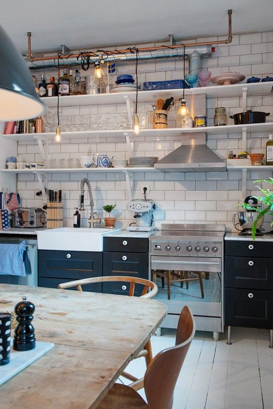Cozy Swedish kitchen design with white tile, black cabinets and wood dining table