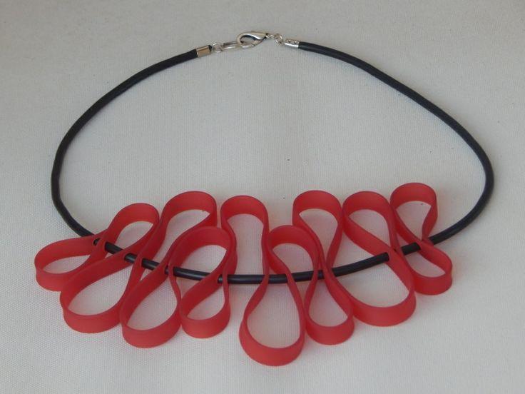 (41) κολιέ από καουτσούκ μαύρο και κόκκινο πλακέ. Το κολιέ αυτό είναι κοντό στο λαιμό.