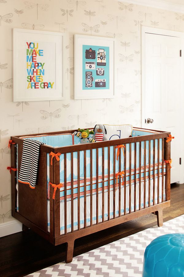 Modern #baby #nursery with colorful #art, dragonfly #wallpaper, turquoise #pouf stool, and #chevron rug.