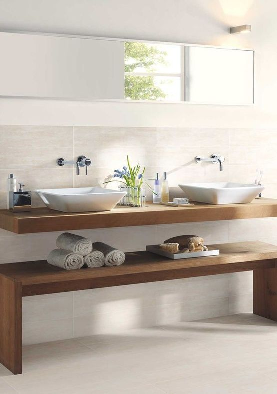 Floating vanity with raised vessel sinks create a sleek, clean, spa-like bathroom.: