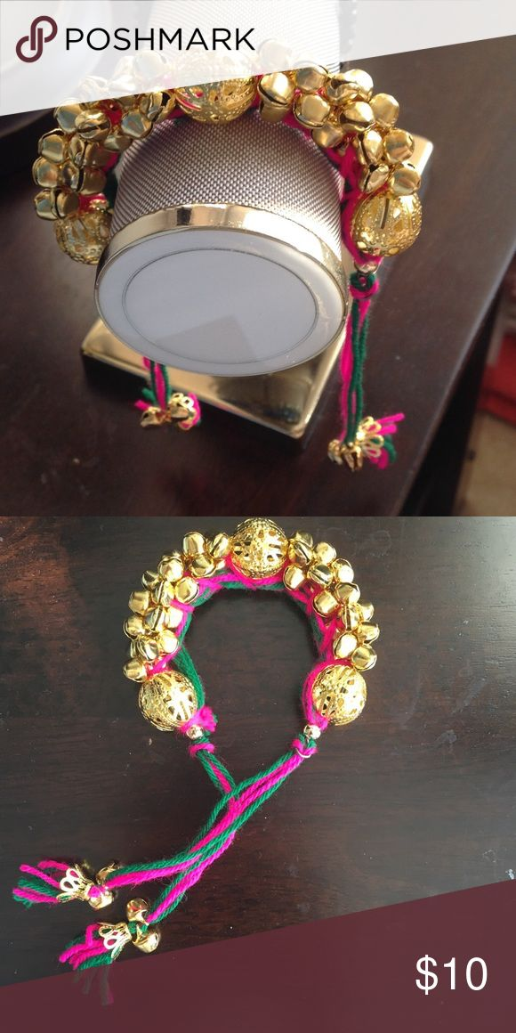 Exquisite Golden Holiday Bracelet!  Celebrate the holiday season with this exquisite golden bracelet with tiable fuchsia and green tassels. The bracelet has small golden bells all around that sparkle and sound every time you move, so go ahead and spread that holiday cheer around! Makes an excellent holiday present for yourself or a friend! I have four available. Price is for one. Jewelry Bracelets