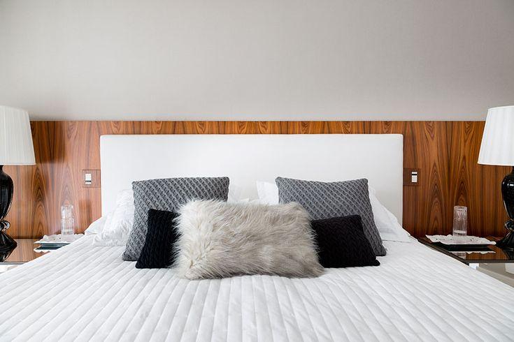 Quarto com painel de madeira, cabeceira branca, edredom branco e almofadas pretas e cinza.