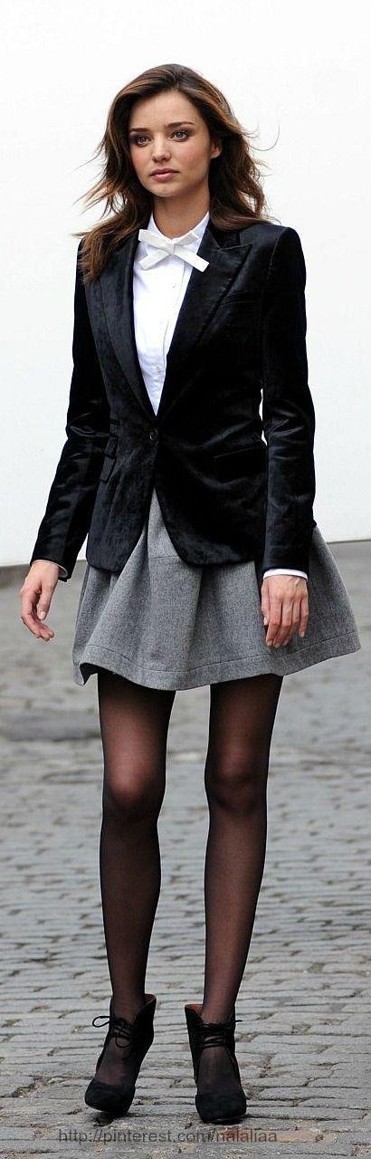 Miranda Kerr looks great in a navy velvet jacket with a grey flared mini skirt & white shirt .